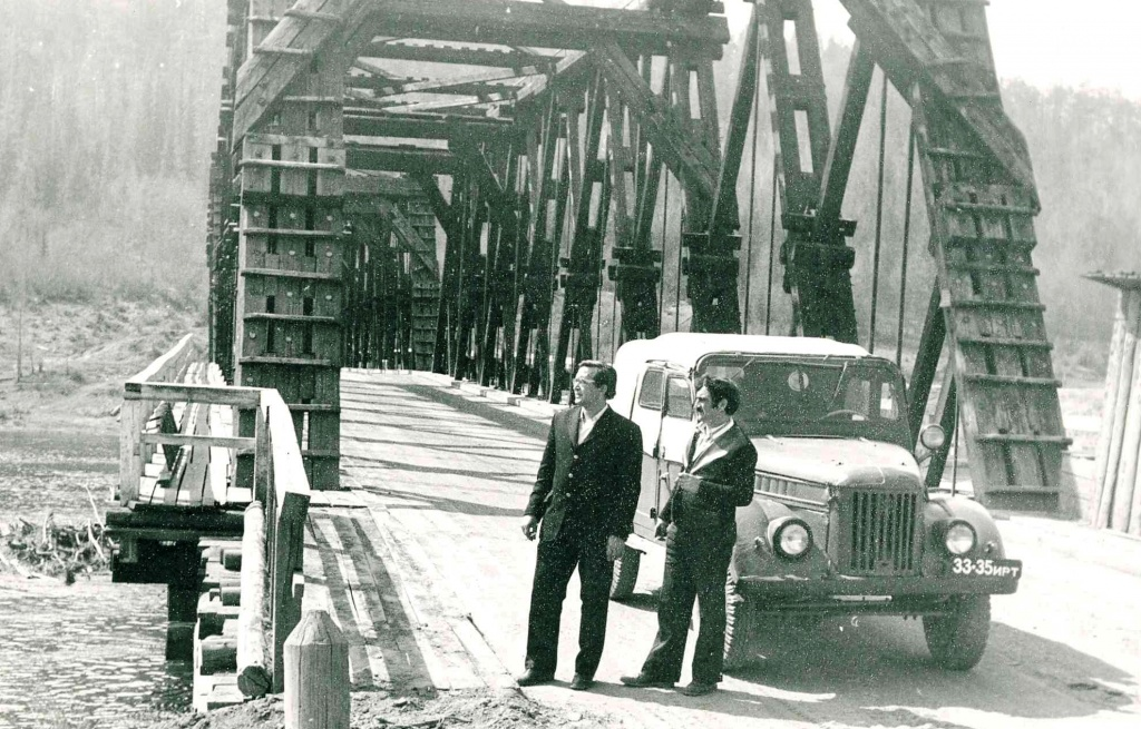 Общий вид деревянного моста через р. Илим в с. Илимск перед затоплением. На мосту слева направо начальник участка Коршуновстроя - Иванов А. и водитель.jpg